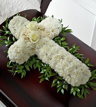 The FTD® Peaceful Memories™ Casket Spray is a gorgeous way to commemorate the faith and devotion of the deceased. White carnations are arranged in the shape of a cross accented in the middle with whit