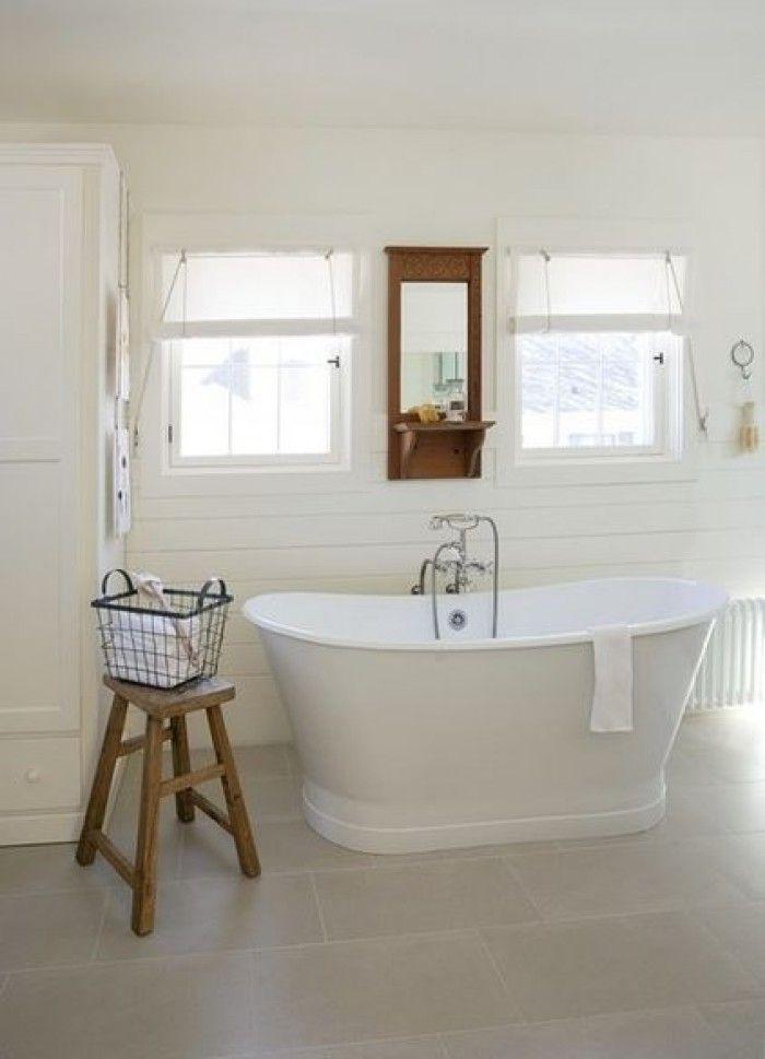 Lichte badkamer met wit houten wanden en vrijstaand bad.