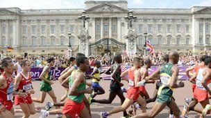 Olympic athletes run past Buckingham Palace