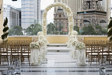 Glass cylinders with candles and flowers lined the aisle of this Las Vegas rooftop wedding.