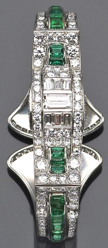 An art deco diamond, emerald and platinum bangle bracelet, circa 1930  of hinged design, the top centering a row of baguette-cut diamonds within old European-cut diamond concave borders and accented by calibré-cut emerald archs, the shoulders centering emerald rows within diamond frames and completed by a curved clasp detailed with diamonds;