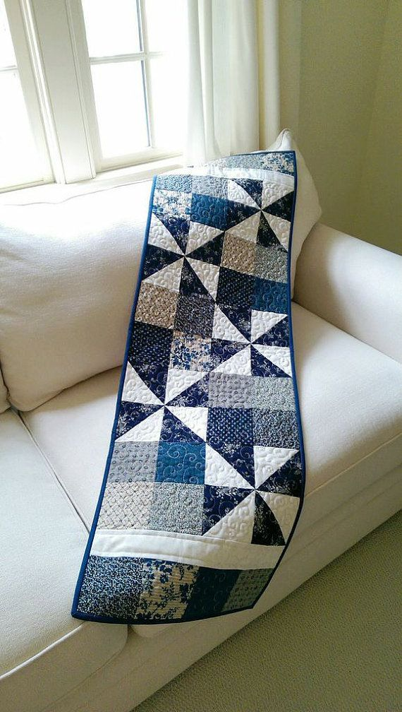 This blue quilted table runner/wall hanging is just the thing for decorating indoors or out. Made from quality 100% cotton fabrics in deep navy blue, medium blues with tans, a cream curling vine for the background, and a small blue check for the binding come together so nicely. The batting is soft 100% cotton along with the creamy muslin backing. It was machine pieced and quilted in a free-motion swirling vine design mimicking the swirling vine in the cream background print. The finished…