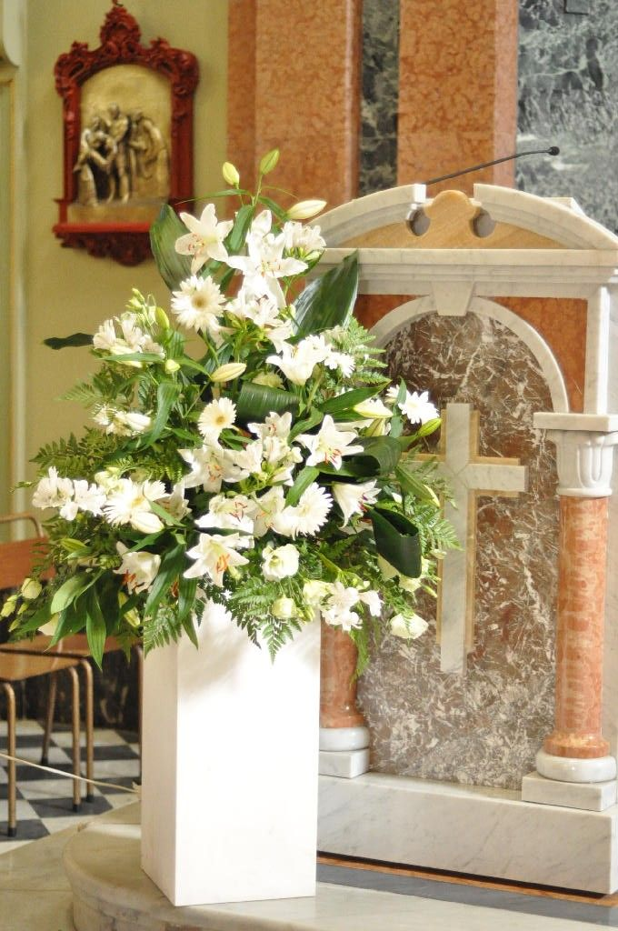 Flower arrangement near the reading stand in white flowers contrasted against the green foliage. The flowers include beautiful and luxurious blooms of white Gerberas and Lilliums.