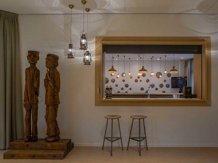 Een houten beeld van Prik en Prak, de smokkelaars uit Overdinkel. Gered uit het afgebrande smokkelmuseum.   Interieurontwerp door Evelien Lulofs voor 't Trefhuus: het Kulturhus in Overdinkel. In opdracht van woningcorporatie Domijn