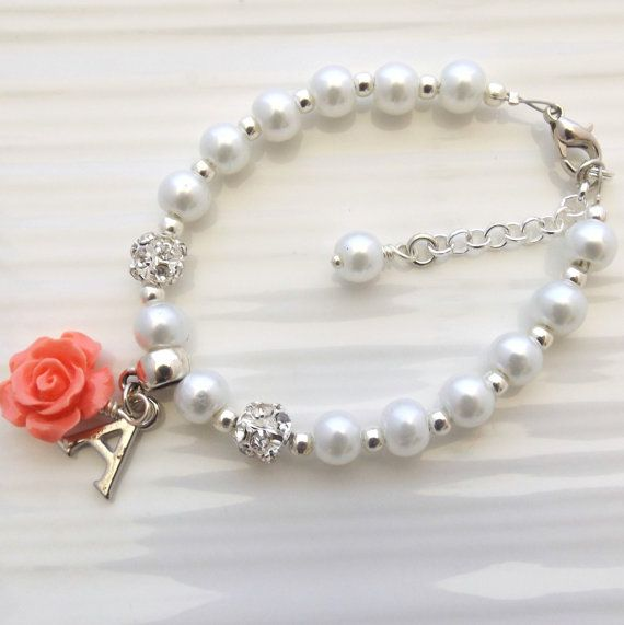 A cute bracelet for your little one made with white glass pearls, grade AAA rhinestone beads a resin rose flower and a metal initial charm of your choice. The flower can be customised to any colour you prefer as shown in the last picture and you can have a choice of white or ivory pearls. A small personalised note can be added to the gift wrapping. At check out please mention: ❤ Name of child ❤ What you would like to say  Please note that colours may vary due to monitor settings.  If you are…