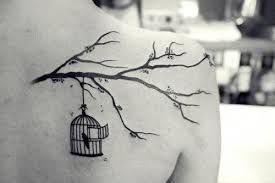 """""""I Know Why the Caged Bird Sings"""". Bird in a cage on a tree branch."""