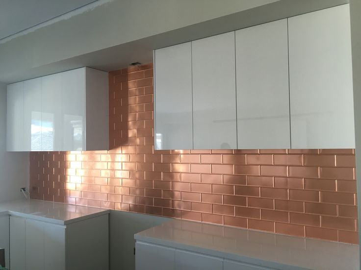 Pressed metal splashback by Sydney Pressed Metal. This is our brick panel pressed into copper. Great selection by owner to combine with white