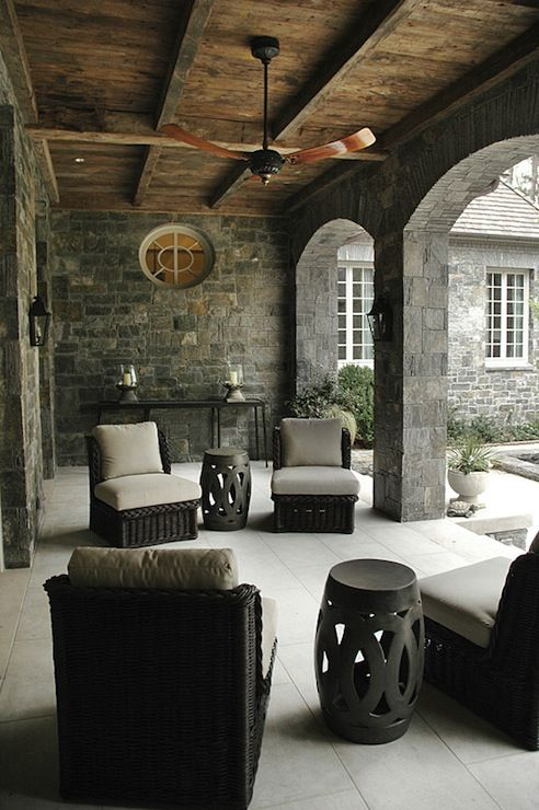 Amazing covered patio with wood plank ceiling. Gray stone walls and arched doorways. Gray outdoor wicker furniture and gray garden stools.