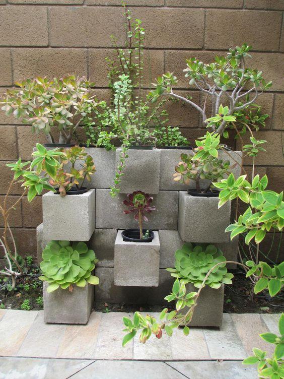 Mur de briques—Ces vieilles briques de ciment deviennent de jolis pots à fleurs une fois empilées les unes sur les autres.