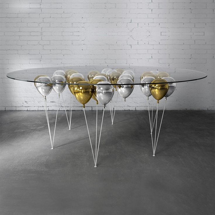 """THE UP BALLOON DINING TABLE 2017 EDITION  """"GROWING OLD IS COMPULSORY, GROWING UP IS OPTIONAL."""" - BOB MONKHOUSE This uplifting design was conjured up by master illusionist Christopher Duffy, working with the concept of levitation and buoyancy. The UP Balloon Table is a playful trompe l'oeil, giving the impression of a glass table top being suspended by gold and silver balloons."""