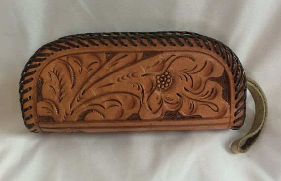Gorgeous hand-tooled leather clutch or glasses case. This item remains in very good condition, but does have some tearing along the zipper. The