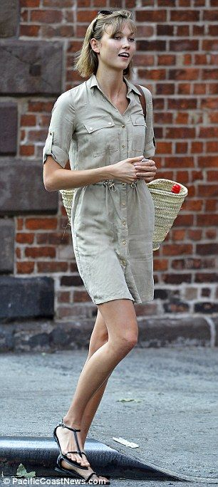 Pin parade: The 21-year-old supermodel's khaki shirt-dress and black T-sandals highlighted her mile-long legs