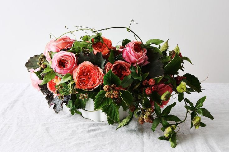 """Nestled in a fluted baking dish, a berry and rose arrangement by Emily Thompson. In this arrangement:  Garden roses """"Romantic Antike"""" Blackberries Passion vine Heuchera (coral bells) foliage"""