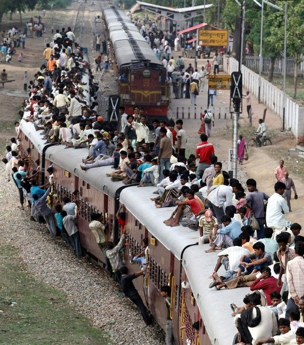 Train transportation in India -- people inside the train, hanging on the sides of the train, & sitting on top of the train. Talk about dangerous!