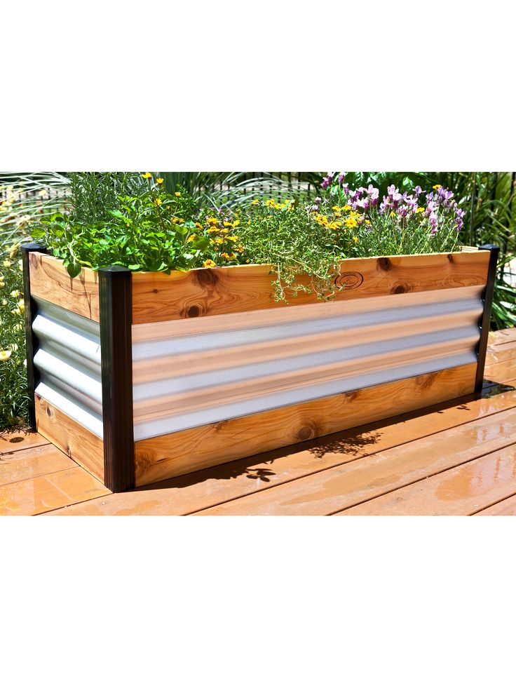 "Corrugated Metal and Wood Raised Bed. This handsome raised bed is made from a combination of wood and metal to achieve a new look in raised bed gardening. You get the warmth of wood with the sturdiness of metal. The long, narrow shape fits in tight spaces and makes a nice addition to the landscape. The bed is ​15-3/4"" deep so you can grow almost anything. ​Patented Swift-Lok post and cap assembly makes set-up easy."