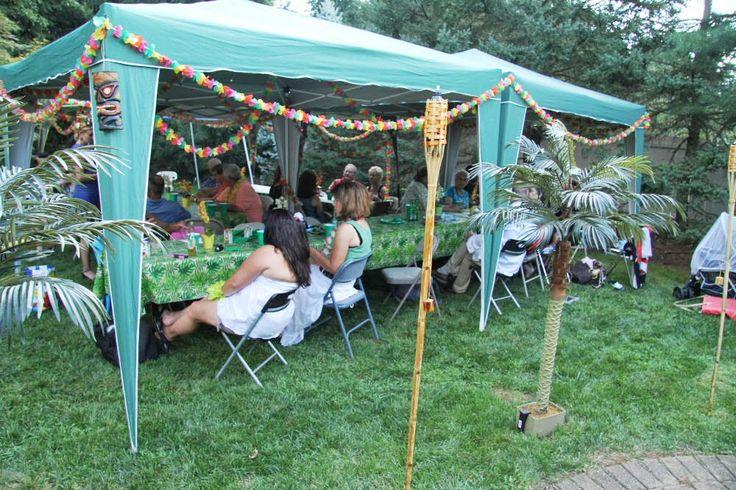 Hawaiian luau backyard tent decorations Tiki, lei, palm trees and