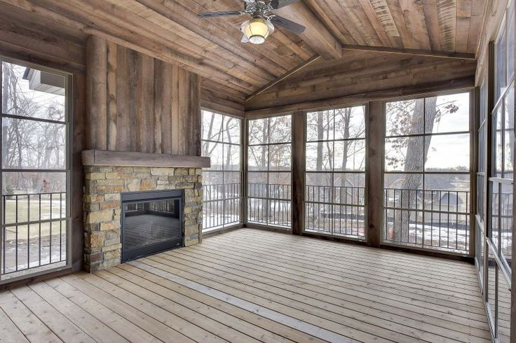 Three season porch off the deck featuring stone fireplace with a reclaimed wood fire mantel - Parade of Homes Model | Creek Hill Custom Homes MN