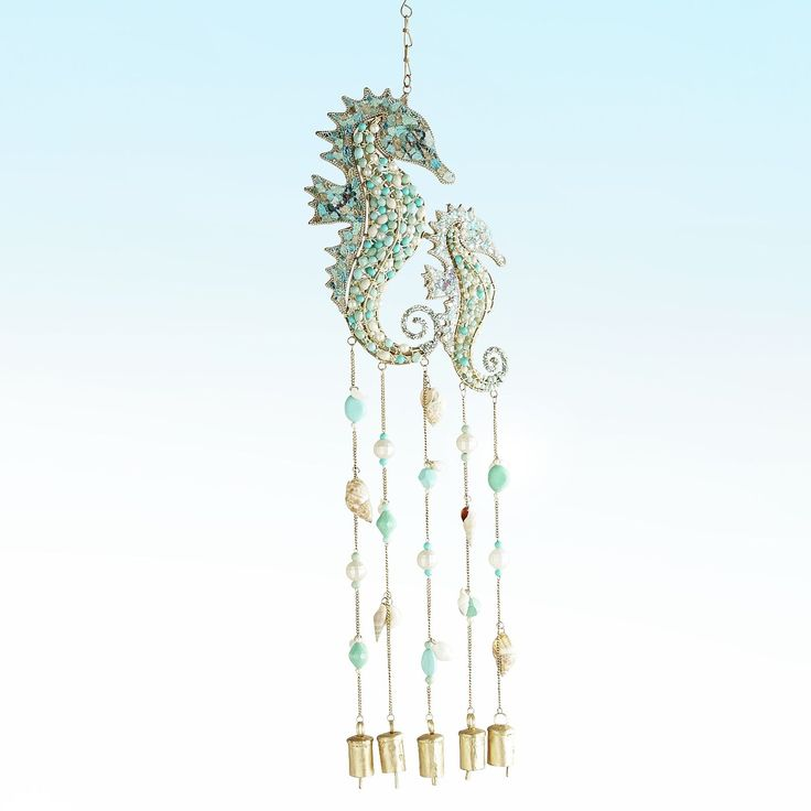 Hear the call of the ocean with our beautifully beaded seahorse wind bells. Two seahorses float above a bevy of shells and bells to bring the sea's song wherever you decide to hang it.