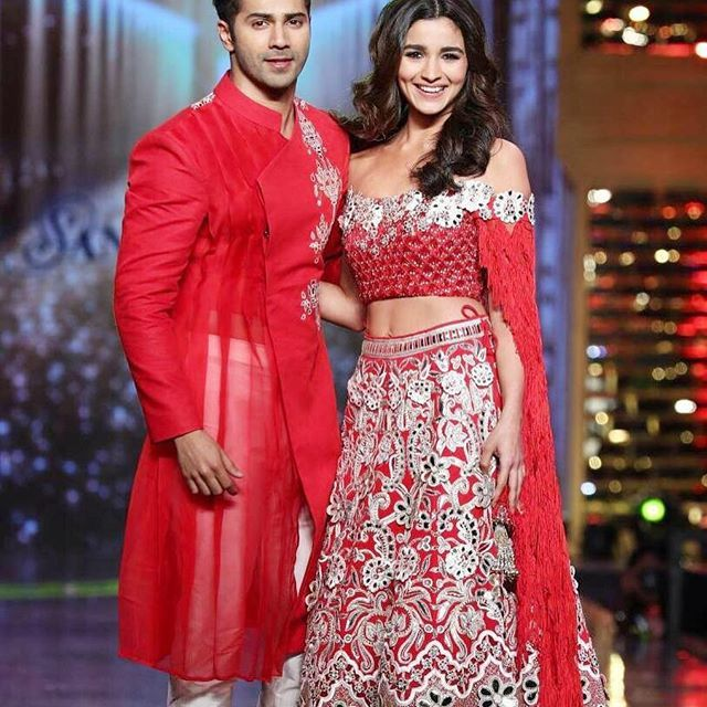 Alia in a red lace lehenga embellished with Swarovski crystals, mirror and resham work and a tasseled off-shoulder choli by Abu Jani Sandeep Khosla #abujanisandeepkhosla #abujani #sandeepkhosla #aliabhatt #varundhavan #fashionshow #bollywoodweddings #bollywoodnews #celebweddings #celebbride #weddinginspo #sherwani #bollywood #indianwed...