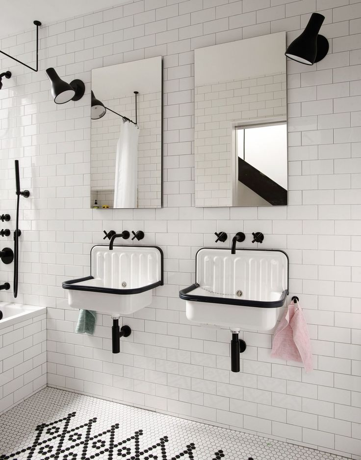 Upstairs, the bathroom is brimmed with white tiling and black accents. Two sleek wall mirrors are placed above a set of wall mount sinks while existing taps are painted in a matte black finish.