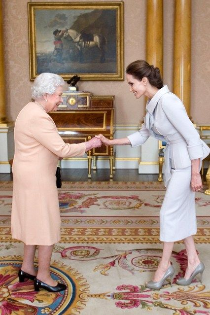 Angelina Jolie is presented with her honorary damehood by the Queen at Buckingham Palace - she is the first American woman to ever receive the title.