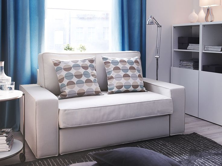A Living Room With A Two Seat Sofa Bed Covered With A Beige Fabric Together  With A White Storage Combination With Doors Part 85