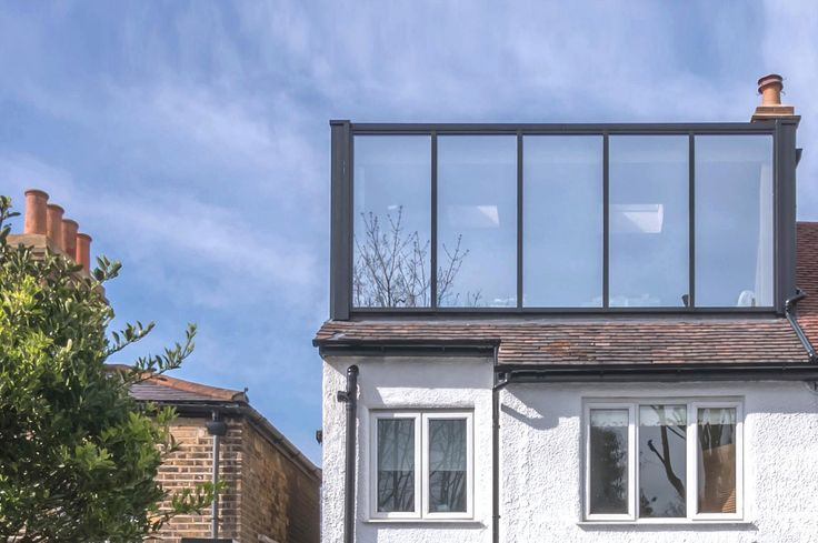 Modern loft extension with ebony stained larch cladding and black aluminium glazing system