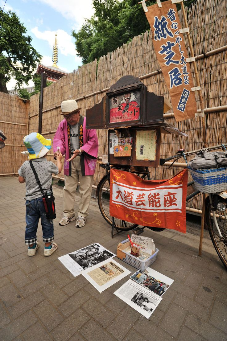 Kamishibai storyteller and his scrolling picture theater mounted on his bicycle.