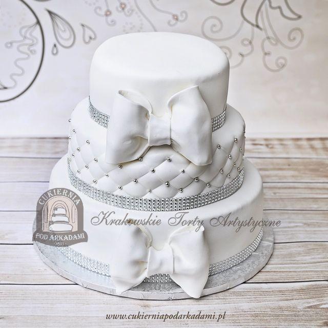 15BW Tort weselny piętrowy z kokardami, kryształkami, koralikami i pikowaną polewą. Multi-tier white wedding cake decorated with crystals and sugar bows.