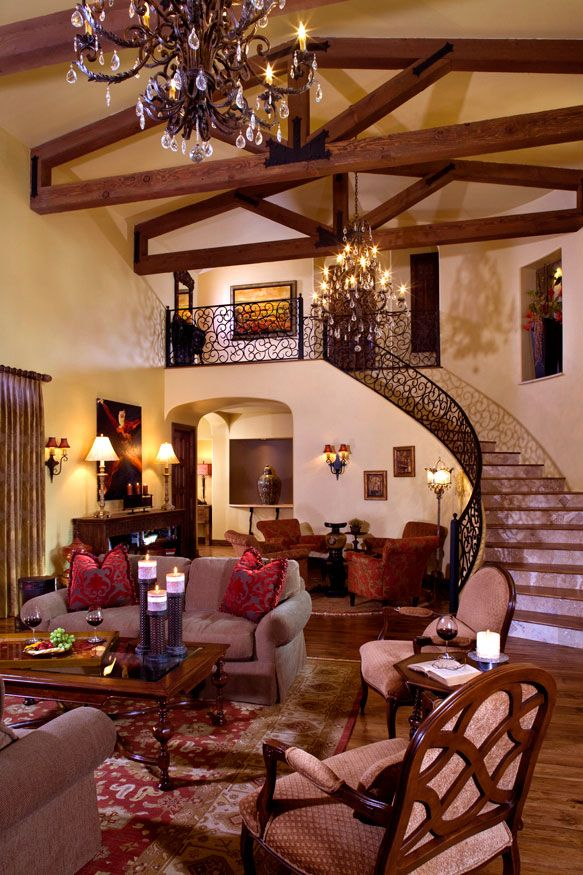The grandeur of this formal living room is unmistakable. Soaring cathedral ceilings with exposed wood trusses are accented with sparkling iron and crystal chandeliers. The scrolled iron railing is detailed and delicate on the curving grand staircase. Custom draperies, artwork, lighting, furniture, and accessories round out this beautiful space. Design by VM Concept in Scottsdale, AZ. Interior Design, Family room, Staircase, Iron railing, Beams, Chandelier, Custom furniture