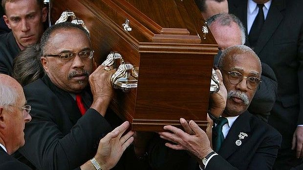 U.S. Olympians Tommie Smith and John Carlos act as pall bearers in 2006 for fellow Olympian, Australian Peter Norman. These three 200 meter runners stood on the medalist podium together at the 1968 Mexico City Olympics. Smith and Carlos raised black-gloved fists during the American national anthem to draw attention to inequality in the U.S. Peter Norman stood in solidarity and also wore a Project for Human Rights Badge. They remained friends long after the Olympics.