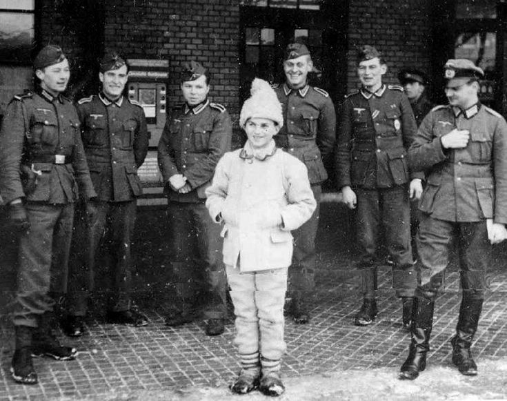 German soldiers look at a Romanian boy wearing traditional folk clothing, which was still common in rural areas of Romania.  (October, 1940)