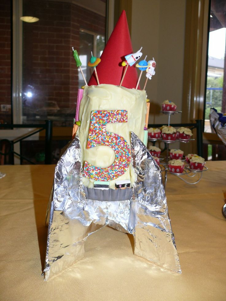 Rocket ship - cheated and decorated a jam roll cake. The base is just cardboard covered in foil.