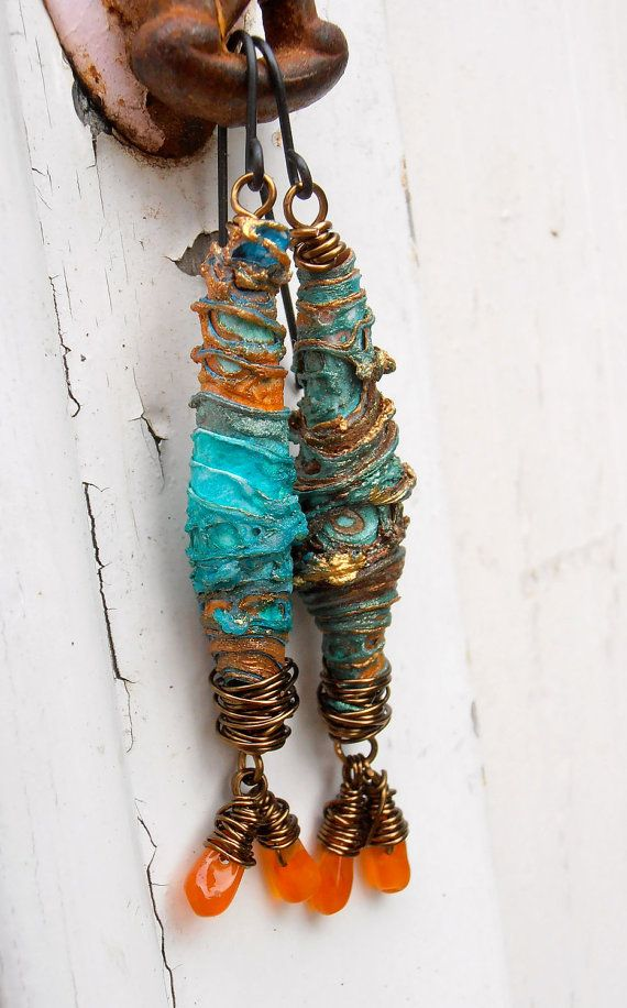 beautiful and unique beads made from paper, fabric and paint in sparkling shades of azure, burnished gold, teal and turquoise hang from antique brass ear wires. i have connected them using fine antique bronze wire, and tiny carnelian briolettes hang from each earring. unique and striking -