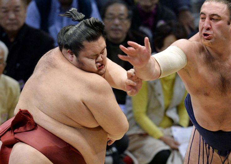 Sumo wrestler Chiyomaru (left) gets a slap from Georgian-born Tochinoshin at the Kyushu Grand Sumo Tournament in Fukuoka, western Japan Picture: AP Photo/Kyodo News
