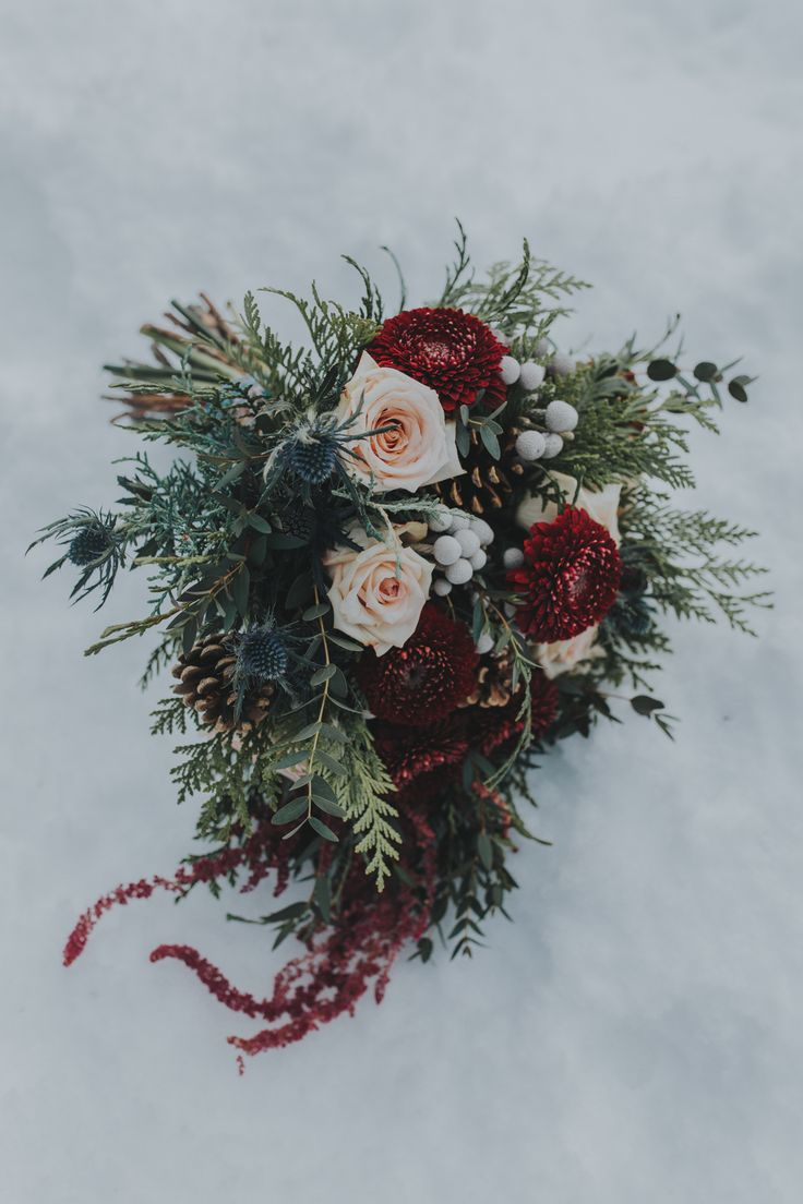 A winter bouquet in the snow with burgundy and champagne blooms and mixed foliage for a winter wedding at Emerald Lake Lodge in Field, BC.  Photo: http://enterthekingdom.ca/ Florals: www.flowersbyjanie.com