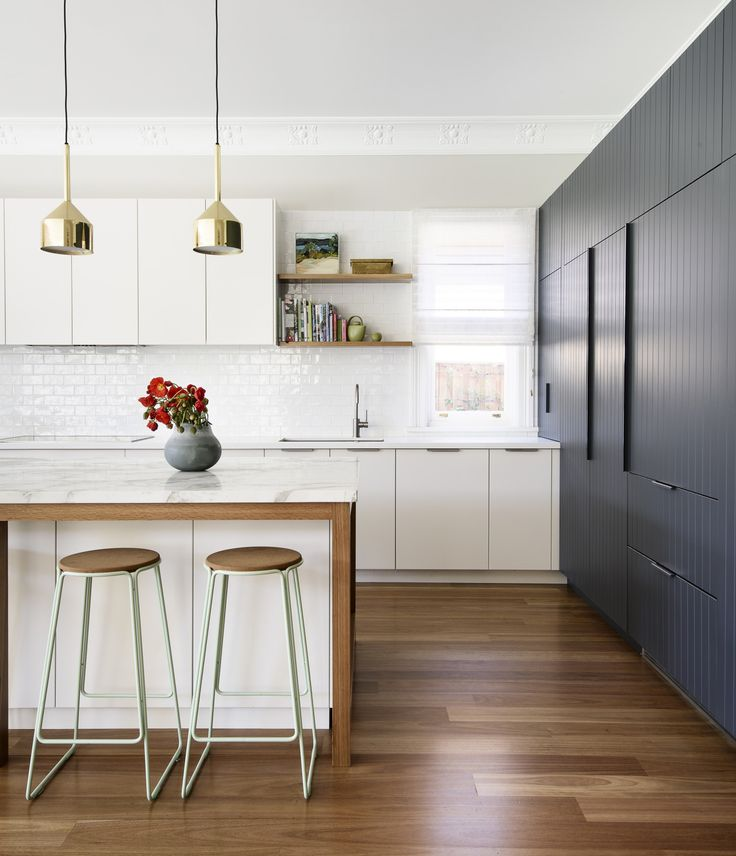Modern brass plated pendant lights adding a pop of gold to this stunning kitchen.