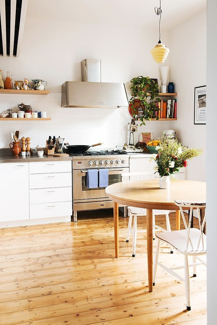 Scandinavian Kitchen with Pine Wood Flooring containing: Wooden Round Table with White Kitchen Cabinet also Open Shelving plus Wall Mount Hood together with White Stools