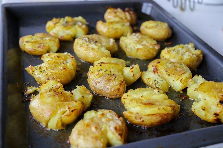 """Kraschad potatis är ett fantastiskt gott tillbehör till maten. Det är precis som det låter, potatis som """"kraschas"""", penslas med vitlökssmör och bakas krispiga och gyllene. Smarrigt! 4 portioner kraschad potatis i ugn 12 st potatisar 100 g smör (1 dl olivolja funkar också bra) 2 vitlöksklyftor 1 msk torkad eller färsk rosmarin Salt & peppar Gör såhär: Koka potatisarna mjuka med skal, låt rinna av. Värm ugnen till 200°. Smält smöret och blanda med pressad vitlök, salt och peppar. Lägg potat..."""