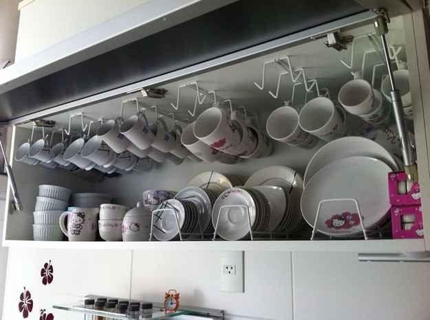 Ganchos para pendurar xícaras e apoios para pratos multiplicam o espaço do armário de cozinha.