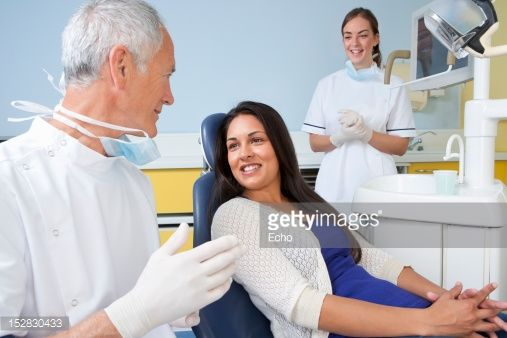 Stock Photo : Dentist talking to patient in dentist's chair