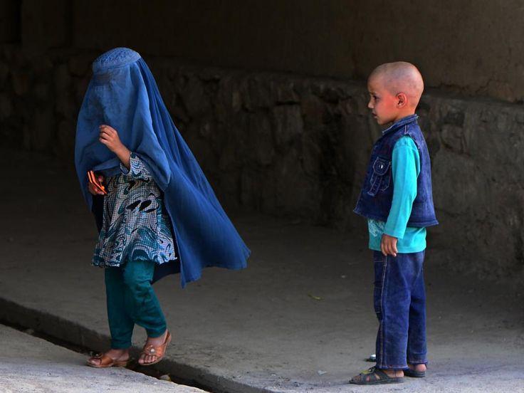 rijdag 22 augustus: Een Afghaans meisje en jongetje staan naast elkaar in Kabul. De Taliban heeft daar besloten dat burka's verplicht zijn voor alle vrouwen.