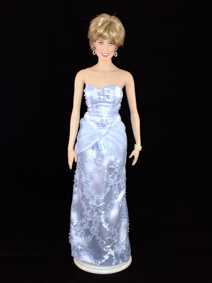 This Franklin Mint Diana doll is wearing a replica of an ice blue silk brocade dress with floral pattern sequins & chiffon by designer Catherine Walker. Princess Diana wore this gown to Nigeria in 1990. Christie's Auction lot 18.