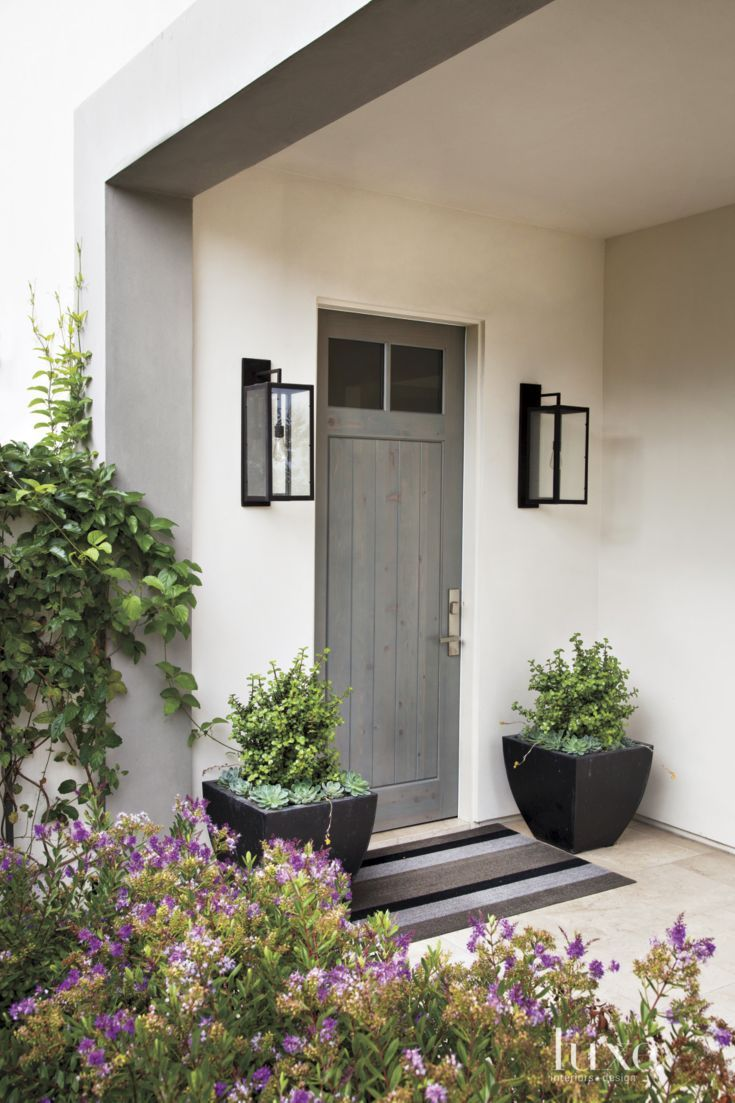 Architect Bill Bocken's riff on the traditional front porch marks the entrance to this Del Mar home. Lanterns from Gibson & Gibson antique lighting flank the front door.
