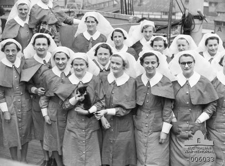 Group portrait of nursing sisters of the 2/7th Australian General Hospital on board the troop transport Acquitania shortly before departure from Australia for the voyage to the Middle East. A nurse in the back row holds a piano accordion. In the front row a kitten is being held, possibly the mascot for the group. Australia: New South Wales, Sydney, Woolloomooloo. February 1941.