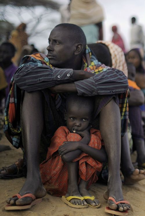 Somali girl taking shelter under her father as they queue for a meal at the dadaab refugee camp in eastern Kenya.