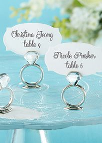 """When it's a ring thing, you want the world to know! Dazzling at bridal showers and rehearsal dinners, this sparkling engagement ring place card holder brighten the room and remind your guests why they're there. Sparkling, double-sided rhinestone mounted in silver-finished metal engagement ring place card/photo holder with slot for place card or photo.  Features and Facts:  Sold in a set of six.  Engagement ring measures 1 1/4"""" h x 1 1/4"""" w.  Uniquely shaped, coordinated place cards included."""