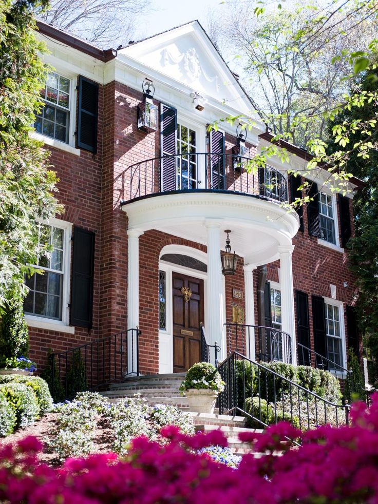 More than 20 interior designers collaborated to turn this dated 1950s Colonial estate into a decked-out showhouse in Washington, D.C.'s Spring Lake neighborhood. The traditional brick home is accented by crisp white columns and trim and black shutters.