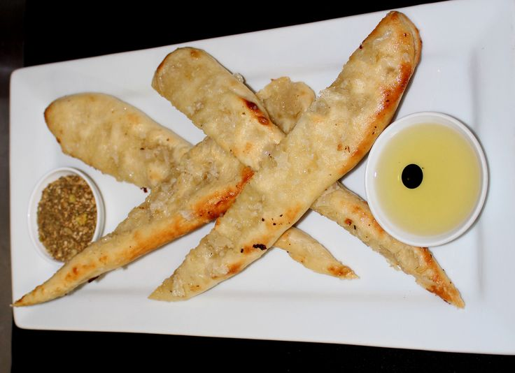 Tomi's Garlic Bread - two freshley baked flat breads drizzled with garlic served with dukkah and dipping oil