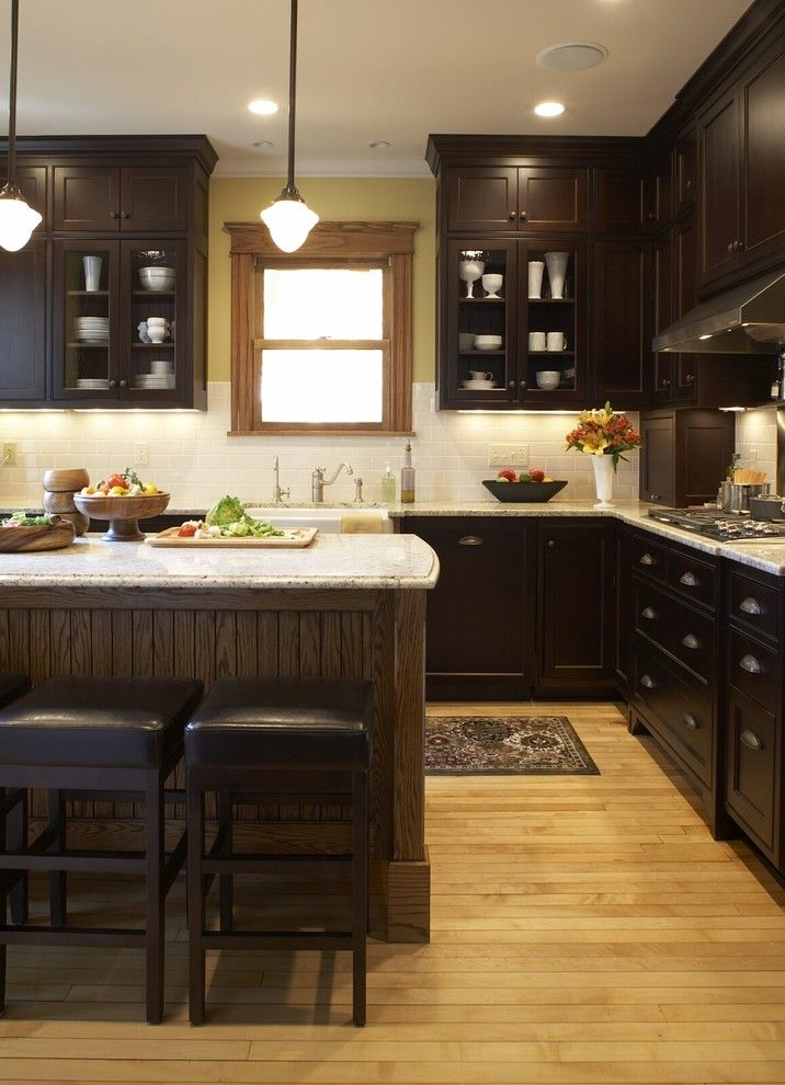 kitchen dark cabinets warm wood floor light counters